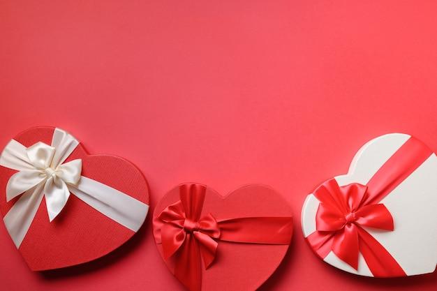 Valentinstagrahmen der roten herzgeschenke auf rot
