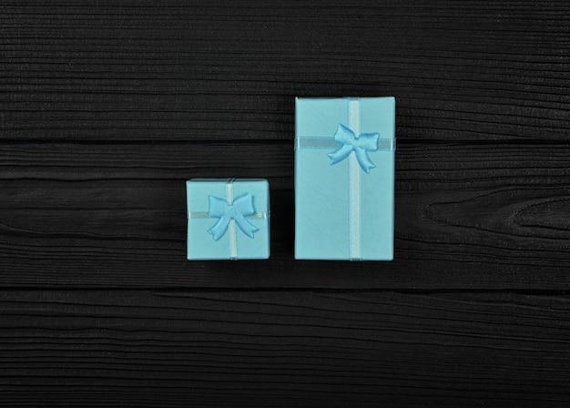 Valentinstagschablone von zwei geschlossenen kleinen blauen geschenkboxen mit bandbögen über schwarzem hölzernem tischhintergrund, nah oben flach liegen, erhöhte draufsicht, direkt darüber