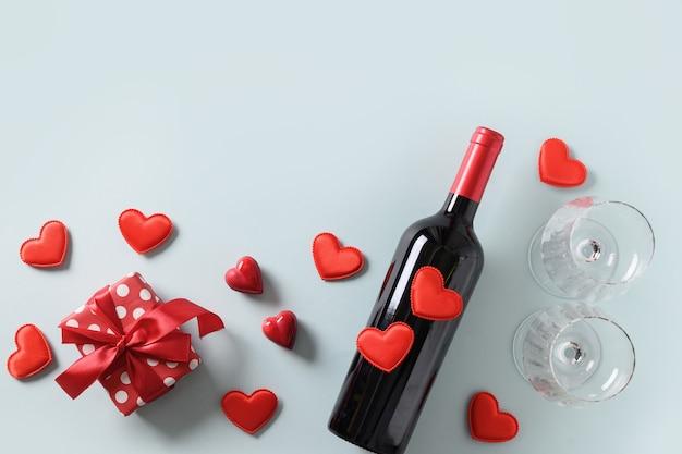 Valentinstagsgeschenk, herzen und rotwein auf blauer, romantischer grußkarte.