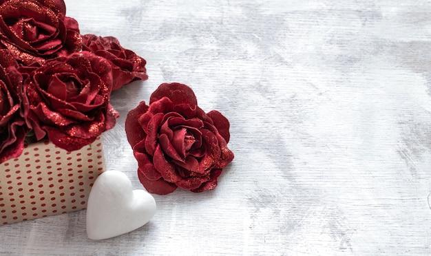 Valentinstagsgeschenk mit dekorativen rosen und weißem herzen