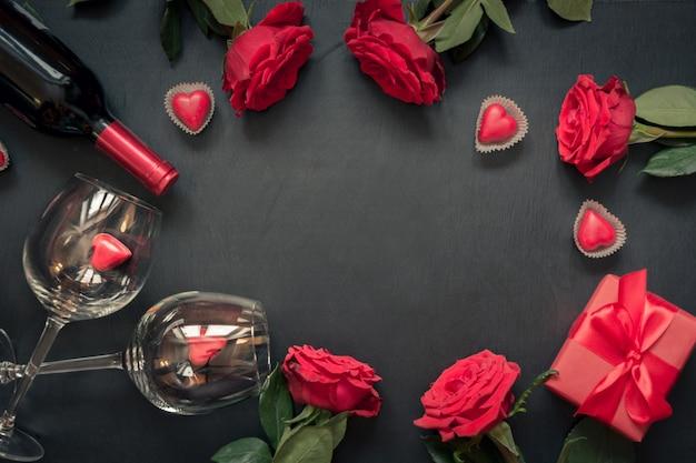 Valentinstagskarte. grenzrot-rosenblumen, rotwein, herzen und geschenkbox auf schwarzem. ansicht von oben. kopieren sie platz.