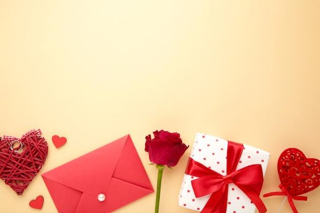 Valentinstagskarte. komposition mit geschenken, roten herzen und rose auf beige. draufsicht