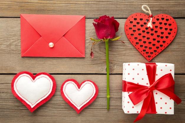 Valentinstagskarte. komposition mit geschenken, roten herzen und rose auf grau. draufsicht