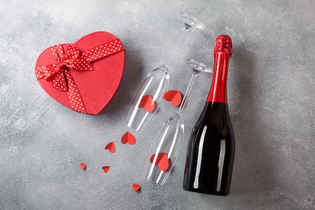 Valentinstagskarte mit einer flasche champagner, gläser mit einer schachtel pralinen in form eines herzens.