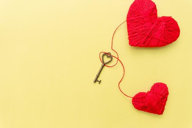 Valentinstagskarte mit roten herzen und schlüssel auf gelbem hintergrund.