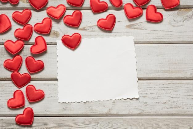 Valentinstagskarte. rote textilherzen mit blatt für ihren text auf weißem hölzernem brett.