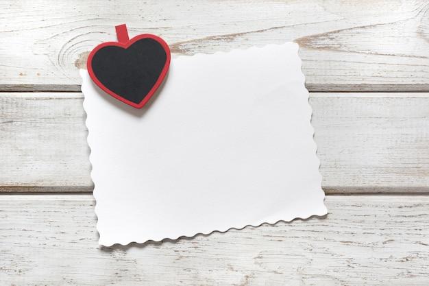 Valentinstagskarte. rote wäscheklammer als herz und blatt für ihren text auf hölzernem brett. copyspace. sicht von oben.