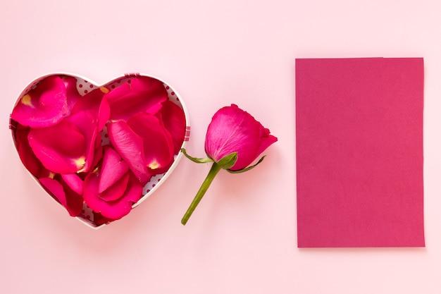 Valentinstagskasten mit den rosafarbenen blumenblättern und papier