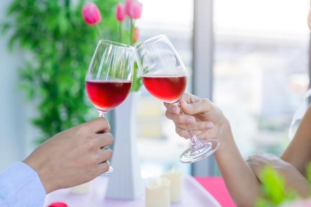 Valentinstagskonzept, nahaufnahme des paares, das das mittagessen mit klirrenden röstenden weingläsern im restaurant romantisch hat.
