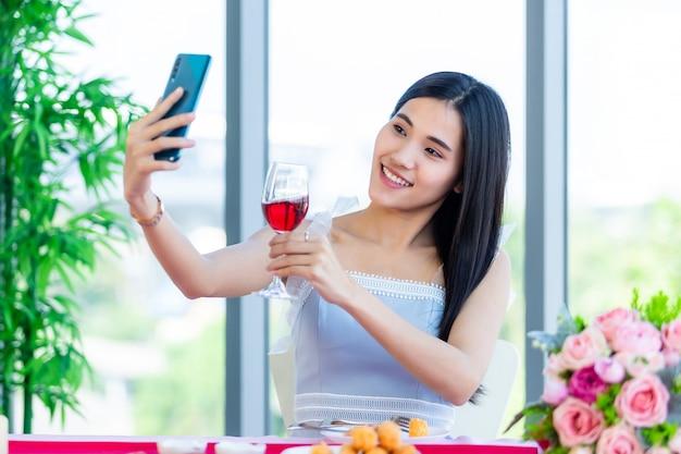 Valentinstagskonzept, selfie von happy der lächelnden asiatischen jungen frau, die an einem tischlebensmittel hält, das mit weingläsern an im restauranthintergrund hält