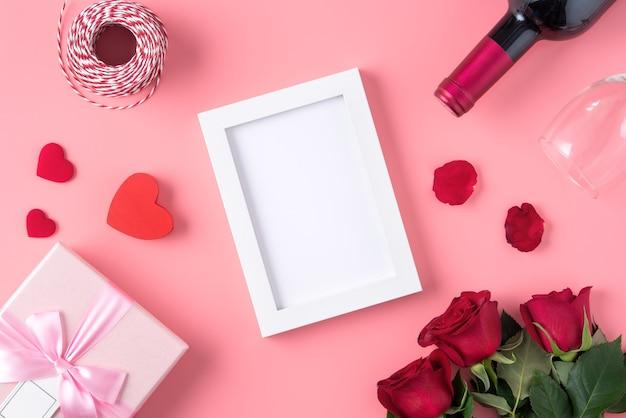 Valentinstagspeicher mit leerem bilderrahmen auf rosa hintergrunddesignkonzept