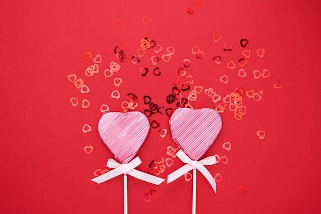 Valentinstagspott oben, rosa lutscher in form des herzens lokalisiert auf rotem hintergrund, mit konfettis, kopienraum.