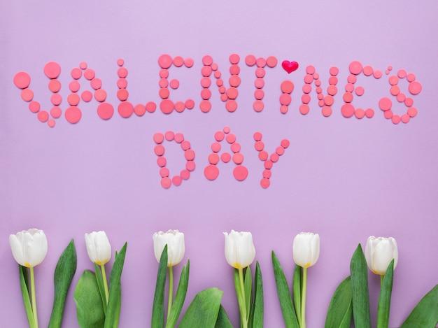 Valentinstagtext auf weichem rosa hintergrund mit tulpen.