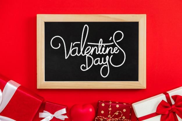 Valentinstagtext mit geschenkboxen auf rotem hintergrund
