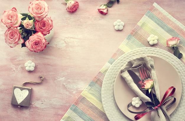 Valentinstagtischeinrichtung, draufsicht über hellrosa hintergrund. hölzerner kalender, serviette und geschirr, verziert mit rosenknospe und bändern, keramischen blumen und rosa rosen.