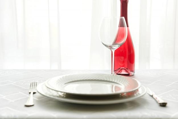 Valentinstagtischgedeck mit rotem champagner. platz für text. einladung zum date.