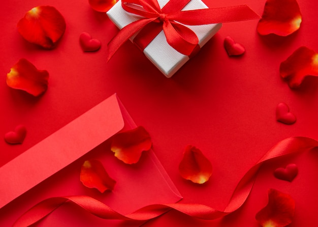 Valentinstagzusammensetzung mit dem roten umschlag, den blumenblättern und der geschenkbox