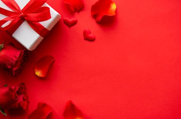 Valentinstagzusammensetzung mit den blumenblättern und geschenk