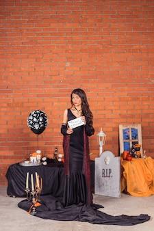 Vampir halloween frauenporträt. schönheits-sexy vampirs-mädchen, mode-kunstentwurf. attraktives vorbildliches mädchen im halloween-kostüm. fröhliche halloween-party.