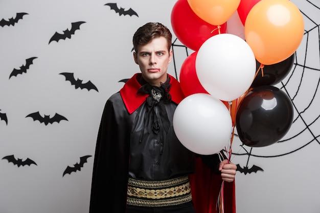 Vampir-halloween-konzept - porträt des schönen kaukasiers im halloween-kostüm des vampirs mit buntem ballon.