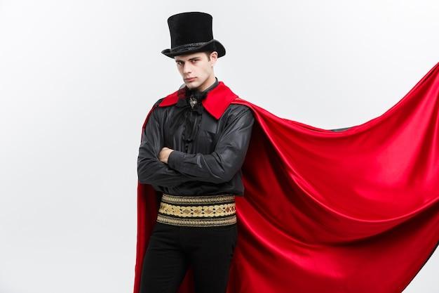 Vampir-halloween-konzept - porträt des schönen kaukasischen halloween-kostüms des vampirs, das seinen roten, schwarzen umhang flattert.