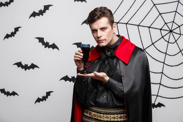 Vampir-halloween-konzept - porträt des schönen kaukasischen vampirs genießen, blutigen rotwein zu trinken.