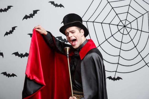 Vampir-halloween-konzept - porträt des schönen kaukasischen vampirs im schwarzen und roten halloween-kostüm, das mit stab singt.