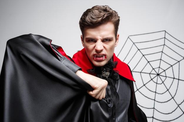 Vampir-halloween-konzept - porträt des wütenden kaukasischen vampirs, der schreit.