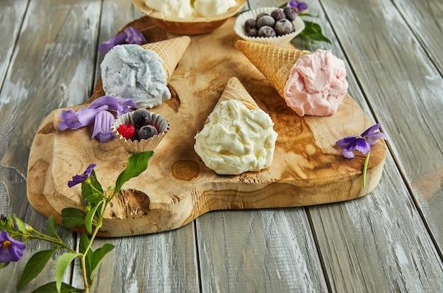 Vanille-, blaubeer- und himbeereis in waffelkegeln auf holzbrett mit beeren und blumen.