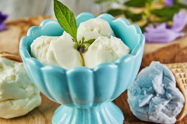 Vanille-, blaubeer- und himbeereis in waffelkegeln und eis in tasse auf holzbrett mit beeren und blumen.