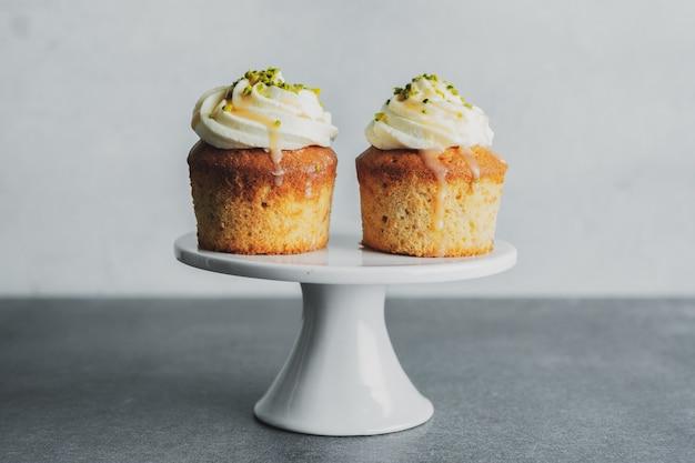 Vanille-cupcakes mit sahne und karamell auf grauem tischhintergrund.