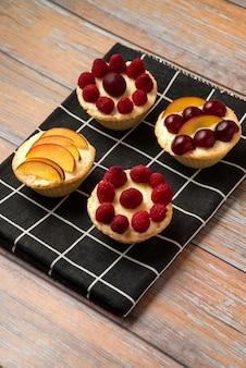 Vanille-cupcakes mit sommerbeerenfrüchten auf dem schwarzen handtuch
