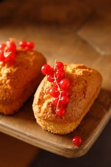 Vanille gebackene cupcakes mit johannisbeeren auf einem holztisch hautnah
