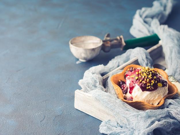 Vanille hausgemachte portionierer in waffelschale mit beerensauce und pistazien. süßes vergnügen