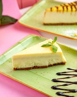 Vanille-käsekuchen mit mascarpone-frischkäse und schokoladensirup auf teller
