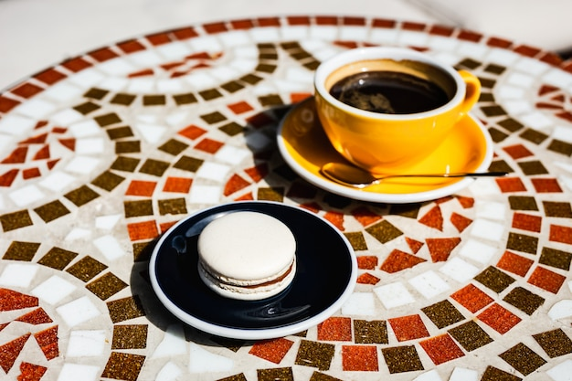 Vanille macaron mit schokolade auf einem teller, eine gelbe tasse schwarzen kaffee, auf einem mosaiksteintisch eines cafés an einem sonnigen tag