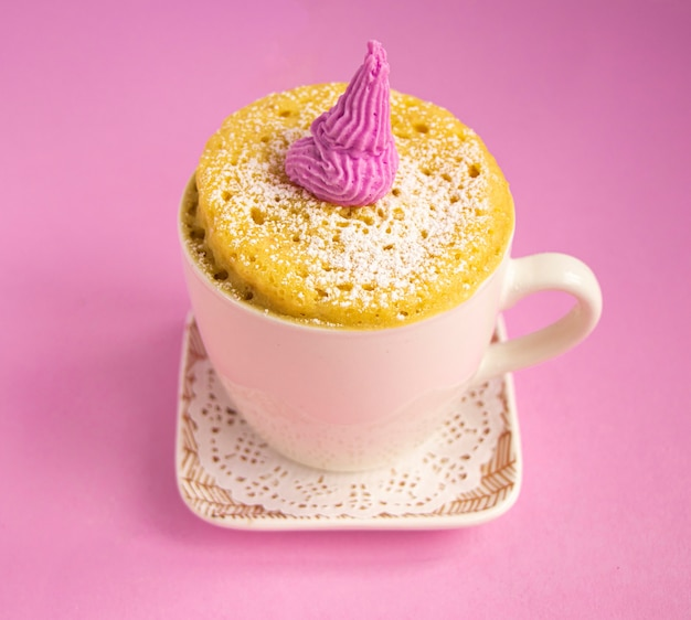 Vanille-muffin in einer tasse ein mini-cupcake in einer tasse auf einer untertasse steht