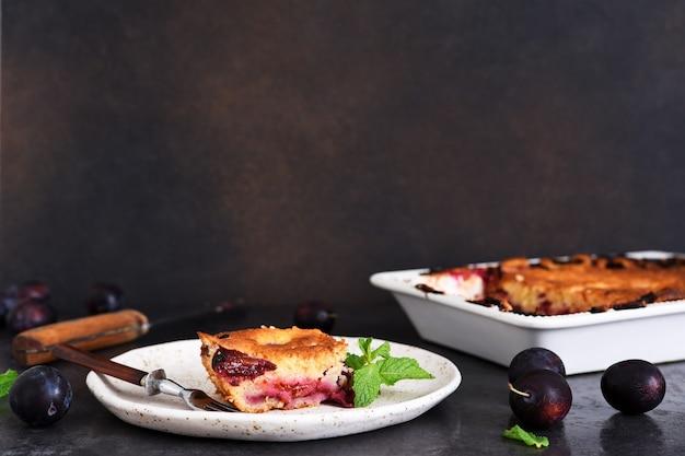 Vanille-muffin mit pflaumen und minze auf dunklem betonhintergrund. früchtekuchen.