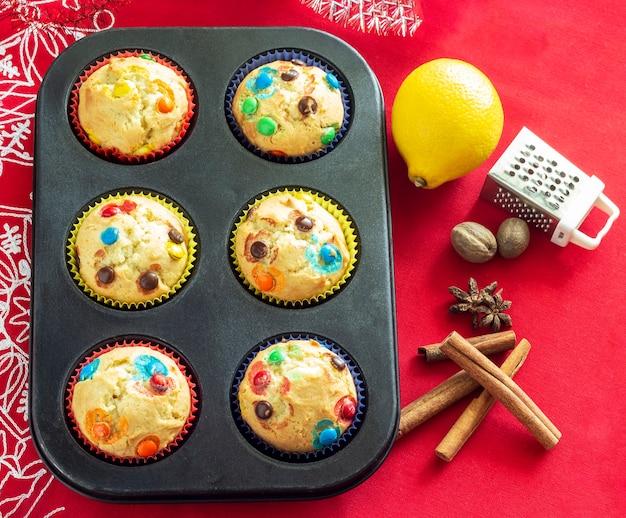 Vanille-muffins mit schokoladensüßigkeit, würzig und zitrone. konzept der weihnachtsbäckerei. ansicht von oben. hintergrund aus rotem sackleinen. platz kopieren.