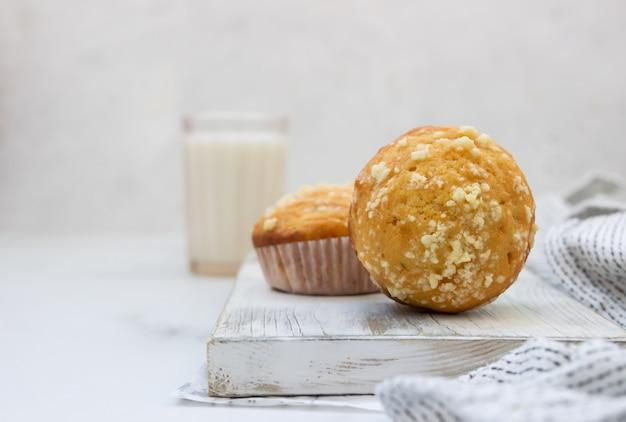 Vanille-muffins und muffins mit streusel in pappbechern mit einem glas milch