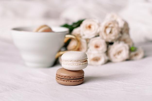 Vanille- und schokoladenmakronen auf weißem rosenhintergrund