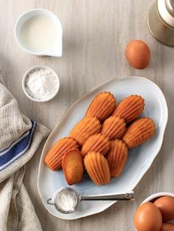 Vanille-zitrone madeleine auf weißer blauer keramikplatte. berühmtes französisches süßes muschelgebäck mit zuckerstaub, serviert mit tee. perfekt für tee- oder kaffeezeit. ansicht von oben