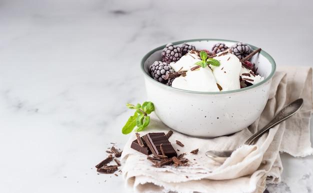 Vanilleeis mit gefrorenen himbeeren, brombeeren, schokolade und minze in einer keramikschale