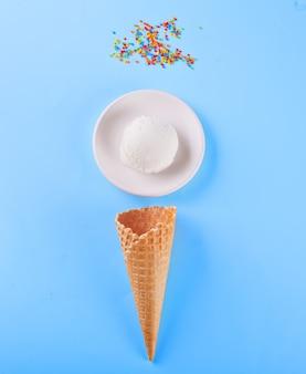 Vanilleeis mit waffelkegeln und süßigkeit auf dem blauen hintergrund