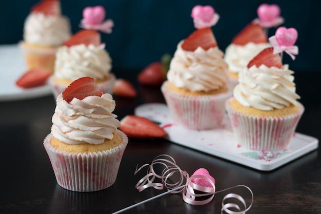 Vanillekleine kuchen mit frischen erdbeeren auf einer dunklen oberfläche