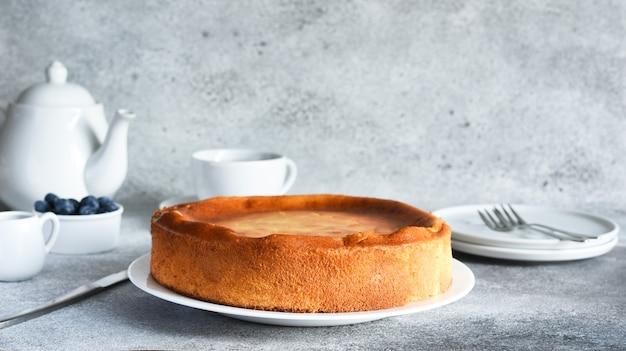 Vanillekuchen auf dem küchentisch mit einer tasse kaffee gebacken. käsekuchen.
