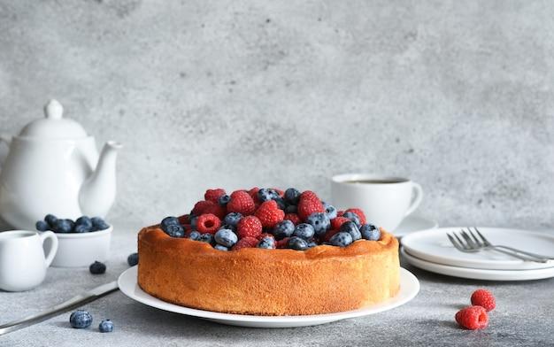 Vanillekuchen mit himbeeren blaubeeren auf dem küchentisch