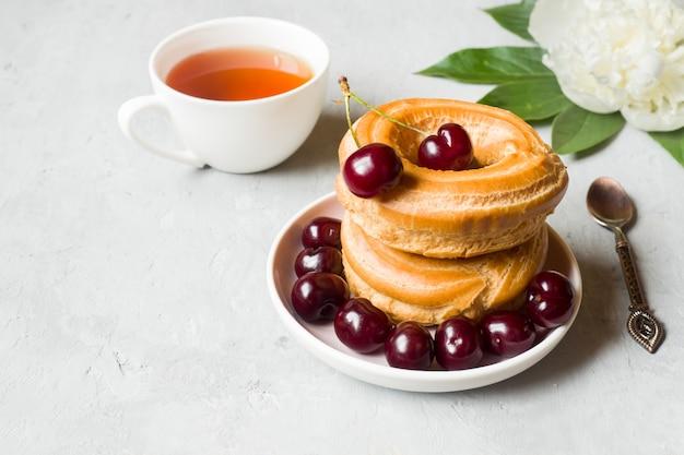 Vanillepudding backt ring mit kirsche auf einer platte auf grau zusammen