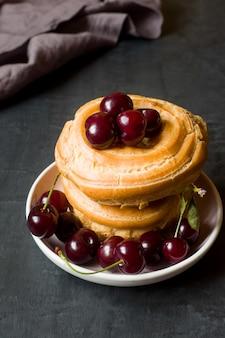 Vanillepudding-kuchenringe mit kirsche auf einer platte eine dunkelheit