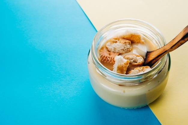 Vanillepudding mit hausgemachtem keks. minimalistischer blauer und gelber hintergrund